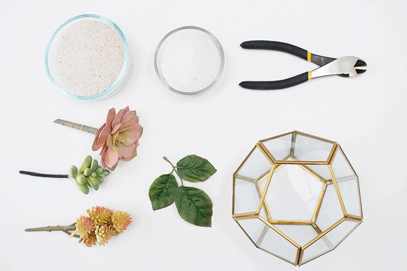 Make an easy succulent terrarium using a few simple materials like faux flowers, sand, and a geometric container.