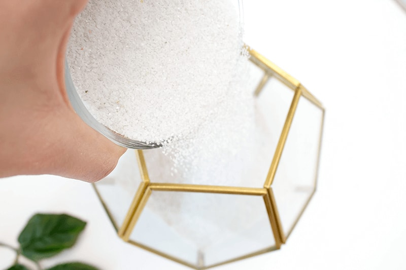 All you need is a geometric glass container, some sand, and artificial flowers to create this faux succulent terrarium.