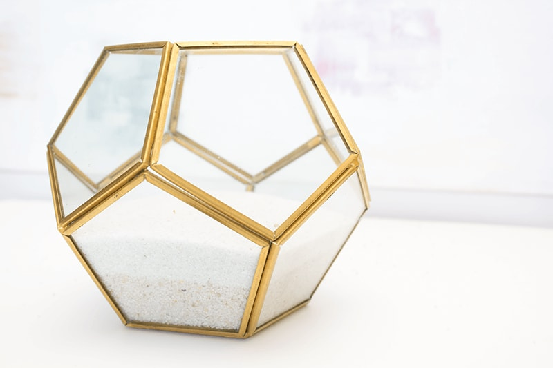 A geometric glass or mason jar with some sand as your base is the perfect foundation for your faux succulent terrarium.