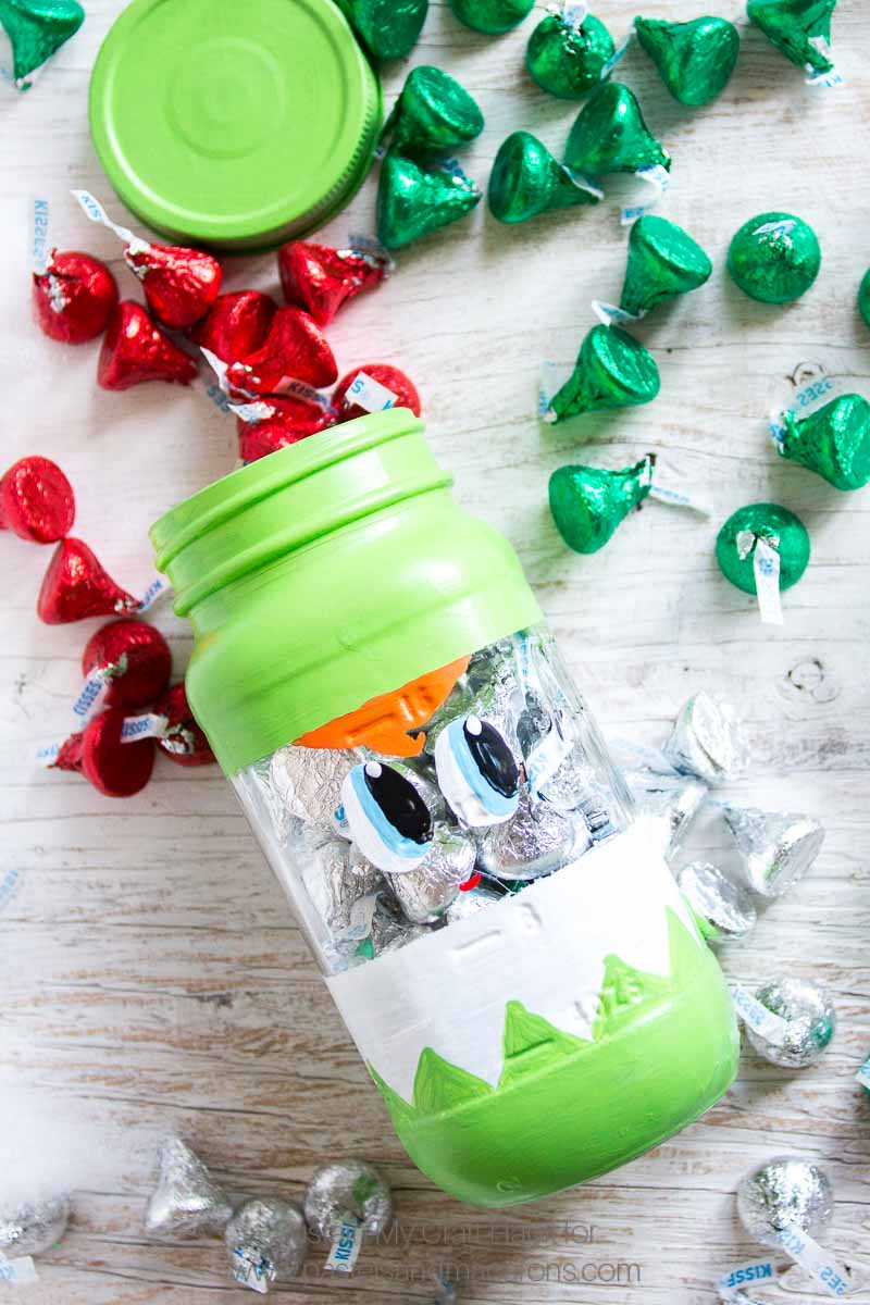 The CUTEST Peak-a-boo Christmas Mason Jar craft ideas | Secret santa gift idea | Handmade holiday stocking stuffer- Painted Mason Jar Christmas Gift you can pop candy and treats into for the holidays. #masonjarcrafts #masonjarcraft #secretsanta #christmascraft #christmasgift #diygift #diychristmasgift #paintedmasonjar